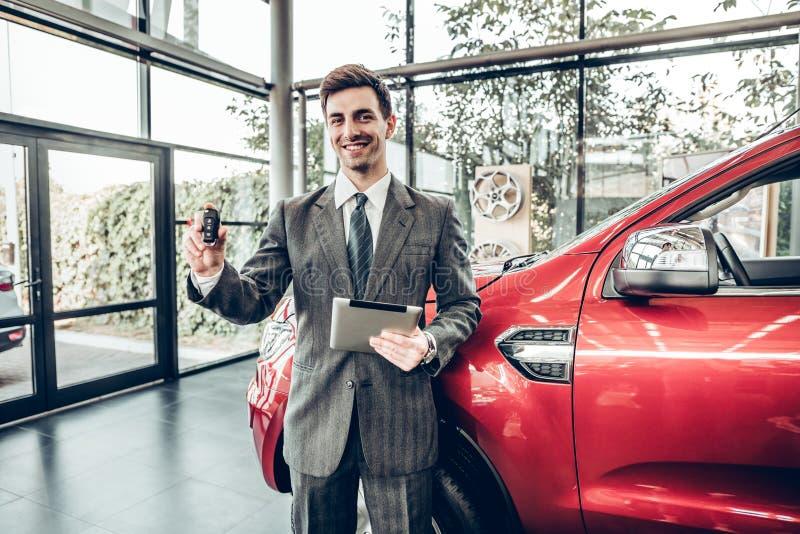 ¡Gran choise! Vendedor de coches clásico joven hermoso que se coloca en la representación que lleva a cabo una llave imagen de archivo libre de regalías