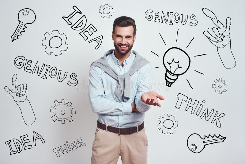 ¡Gran idea! El hombre barbudo encantador en una camisa azul está sonriendo en la cámara mientras que se opone a fondo gris con fotos de archivo