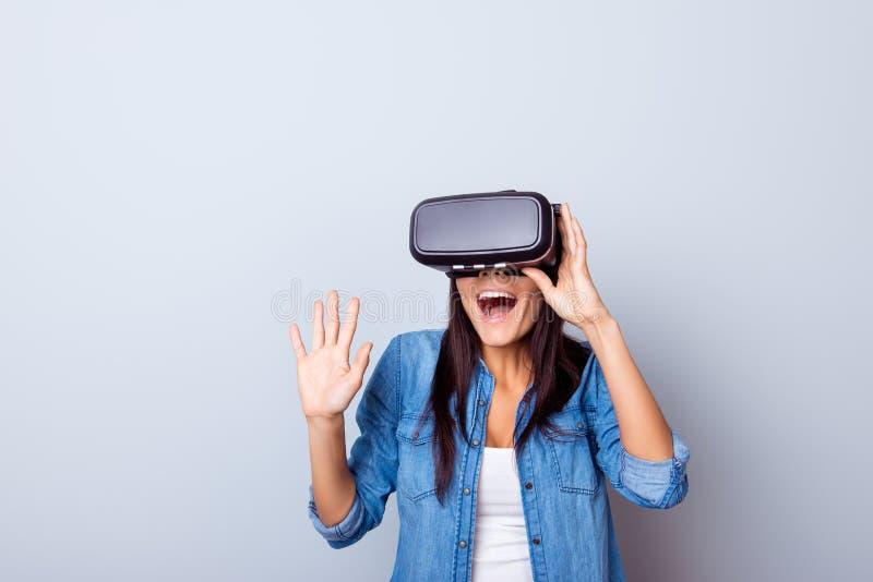 ¡Guau! Muchacha emocionada del latinn en vidrios de un VR sorprendida con qué ella imagenes de archivo