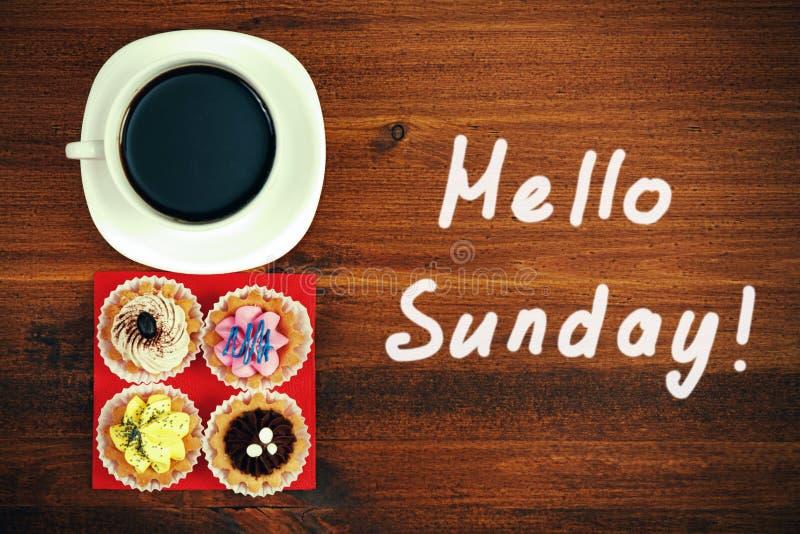 ¡Hola domingo! Taza de té o café y cuatro magdalenas imágenes de archivo libres de regalías