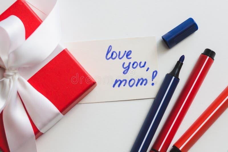 ¡La caja de regalo roja atada con una cinta blanca, los marcadores y una tarjeta con una inscripción 'le aman, mamá! 'en un fondo fotografía de archivo