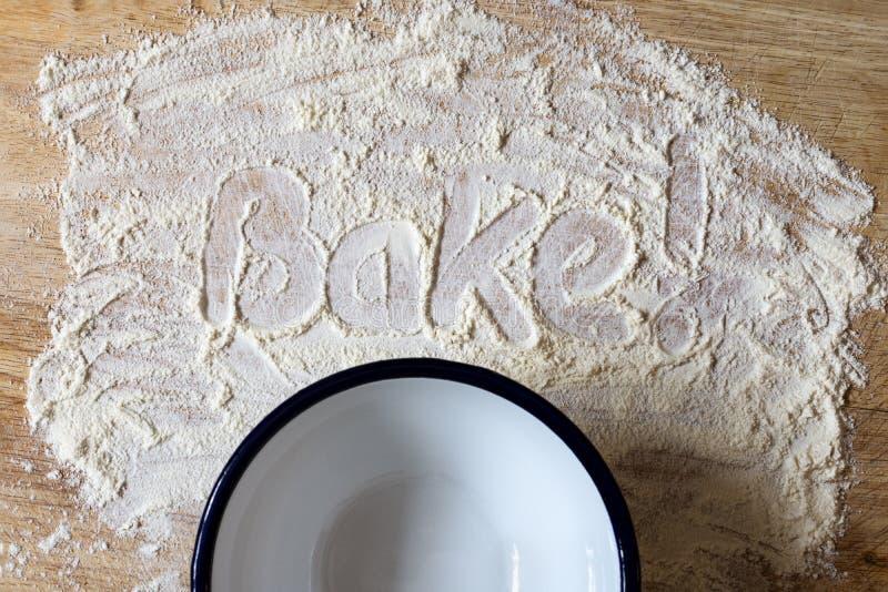 ¡La Palabra Bake! Escrito en una pizarra de madera con bol de esmalte fotografía de archivo libre de regalías