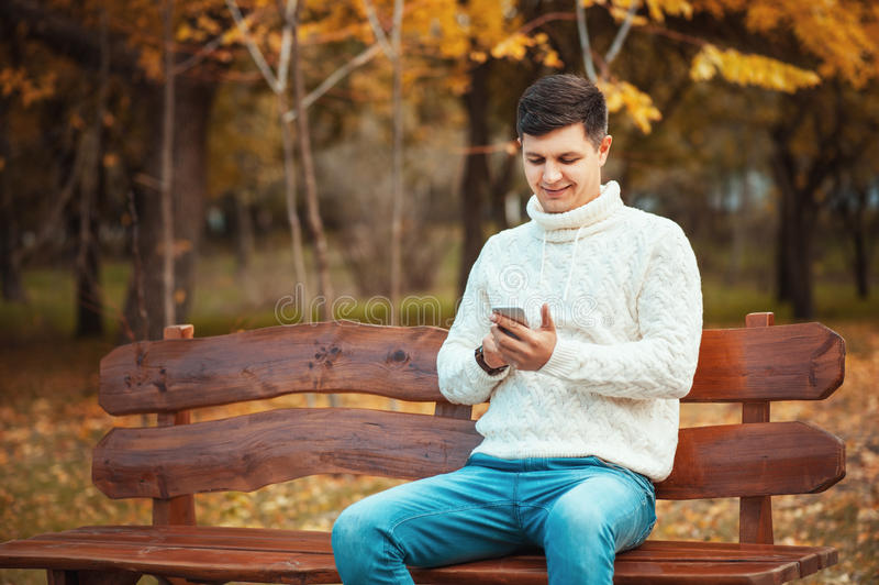 ¡Llame a mí o escriba un mensaje! Hombre joven hermoso en suéter y vaqueros usando smartphone mientras que se sienta en el banco fotografía de archivo