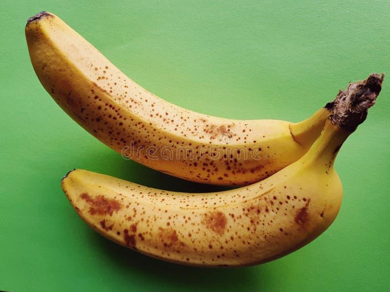 ¡Lleno de vitaminas! Primer de plátanos maduros deliciosos sobre fondo verde fotografía de archivo libre de regalías