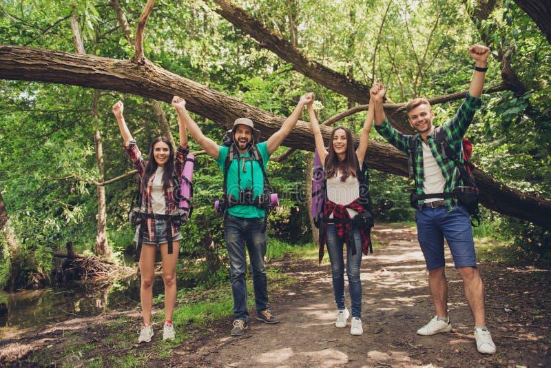 ¡Lo hicimos! Dos pares felices están celebrando el extremo de la ruta orienteering, presentando para la foto Detrás de es la natu foto de archivo