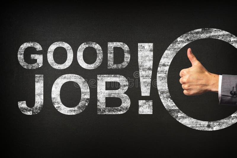 ¡Mano de un hombre de negocios que muestra los pulgares para arriba para el buen trabajo de la frase! escrito en una pizarra fotos de archivo