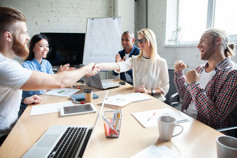 ¡Mi enhorabuena! Dos empresarios alegres que sacuden las manos mientras que estando en oficina así como sus colegas imagen de archivo