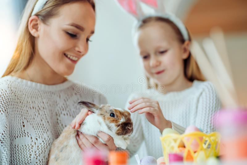 ¡Mire un qué conejo lindo! La pequeña hija con su movimiento de la madre un conejo decorativo casero imagenes de archivo