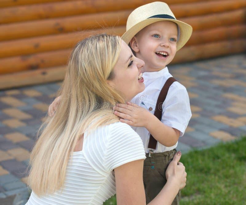 ¡Momento de la vida de familia feliz! El niño pequeño abraza blando a su madre imagenes de archivo