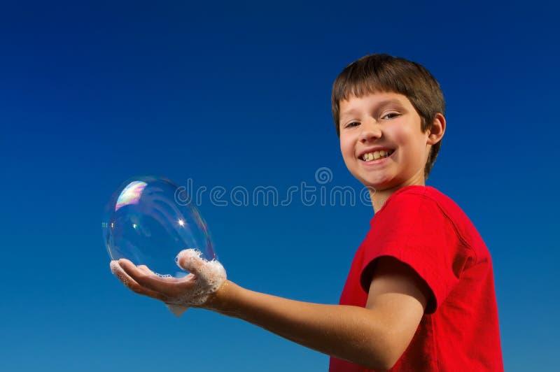 ¡Muchacho soplando burbujas y llevándolas a cabo en su mano! fotos de archivo