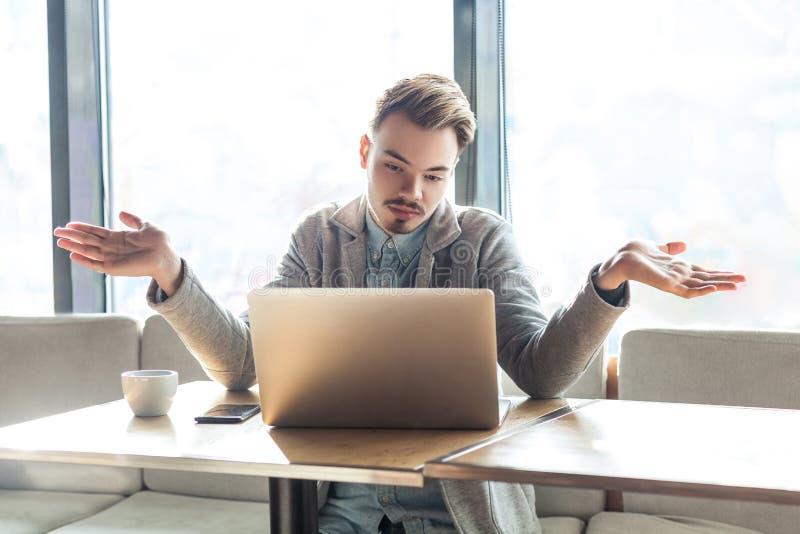 ¡No sé! El retrato del freelancer joven barbudo hermoso confuso en chaqueta gris se está sentando en café y está haciendo la llam foto de archivo libre de regalías