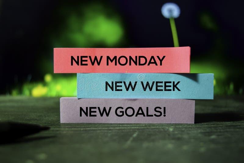 ¡Nuevo lunes, nueva semana, nuevas metas! en las notas pegajosas con el fondo del bokeh foto de archivo