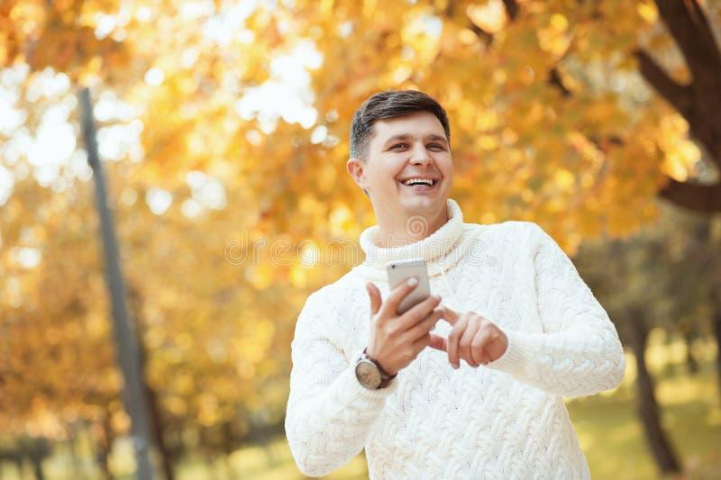¡Otoño anaranjado hermoso al aire libre! Hombre joven hermoso en el suéter que permanece en parque y que usa su smartphone con so foto de archivo