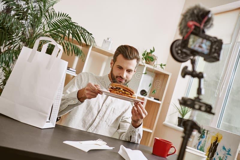 ¡Parece delicioso! Retrato del blogger barbudo de la comida que sostiene una placa con el bocadillo fresco mientras que registra  fotos de archivo