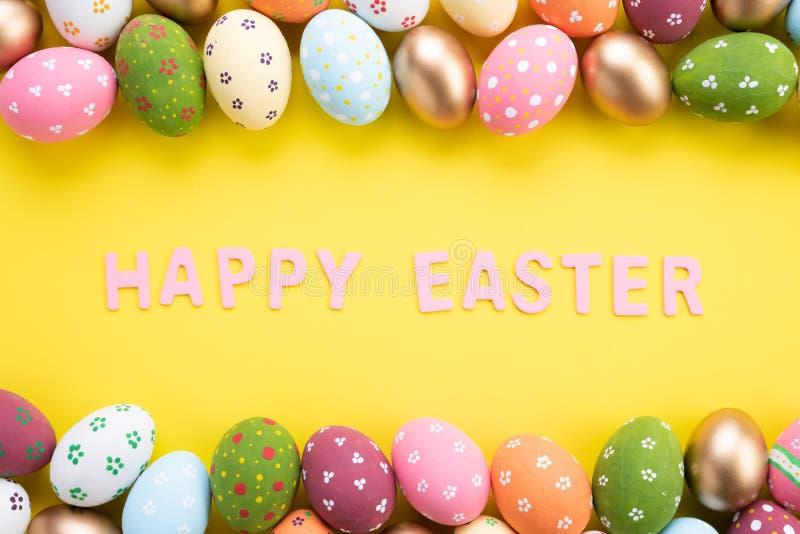 ?Pascua feliz! Cierre encima de los huevos de Pascua coloridos en fondo de papel amarillo Familia feliz que se prepara para Pascu fotografía de archivo