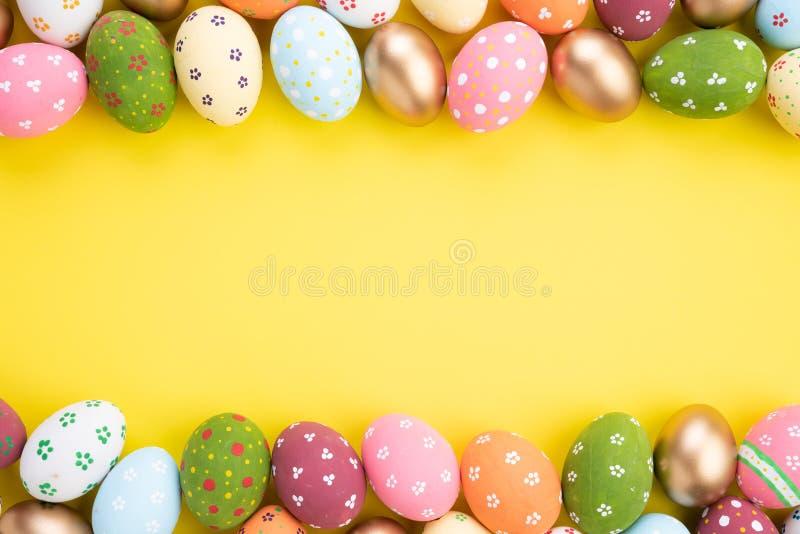 ?Pascua feliz! Cierre encima de los huevos de Pascua coloridos en fondo de papel amarillo Familia feliz que se prepara para Pascu fotos de archivo libres de regalías