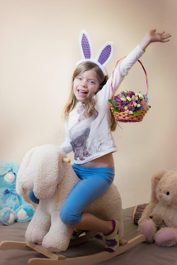 ¡Pascua feliz! La niña monta un conejito mullido con las flores de una primavera en una cesta fotos de archivo