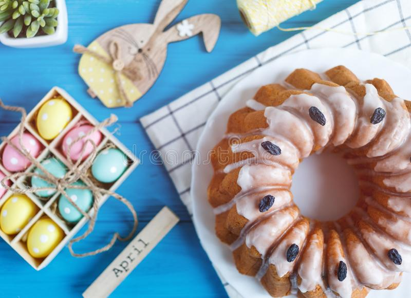 ¡Pascua feliz! Torta hecha a mano en la toalla, huevos, conejo de conejito de madera en fondo de madera azul Decoración para pasc imagenes de archivo