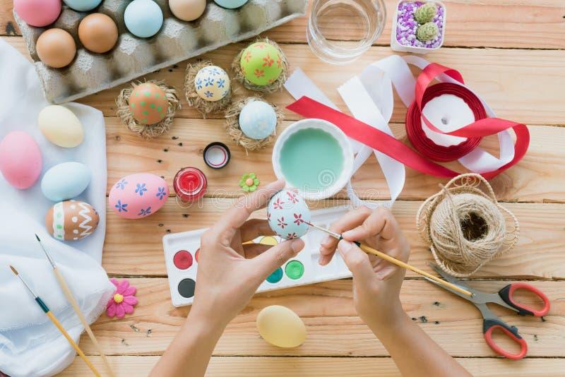 ¡Pascua feliz! Una mano de la mujer que pinta los huevos de Pascua RRPP felices de la familia imagen de archivo libre de regalías
