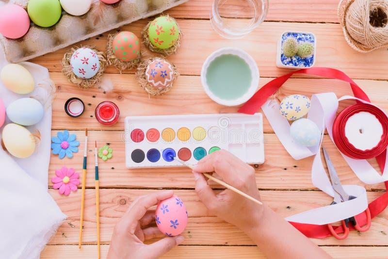 ¡Pascua feliz! Una mano de la mujer que pinta los huevos de Pascua RRPP felices de la familia fotografía de archivo libre de regalías