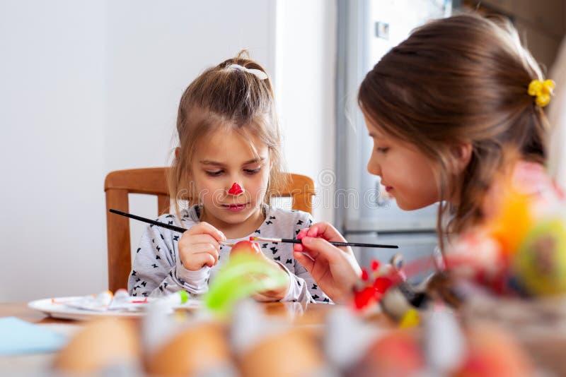 ¡Pascua feliz! Una muchacha del niño hermoso que pinta los huevos de Pascua foto de archivo