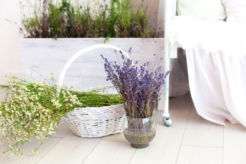 ¡Provence, estilo rústico, lavanda! Una cesta grande con las margaritas del campo y un florero de lavanda están en el piso en el  fotos de archivo libres de regalías