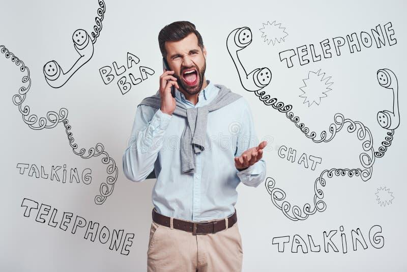 ¡Qué le tienen hecho, oh no! El hombre barbudo enojado está gritando mientras que habla con alguien por smartphone mientras que s fotografía de archivo