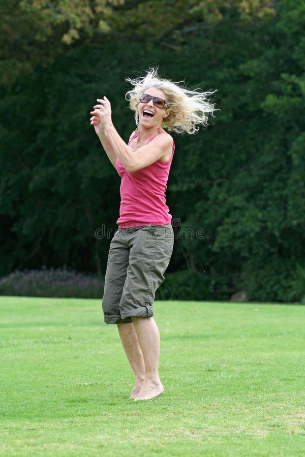 ¡Riendo y saltando, mujer sana que se goza! foto de archivo