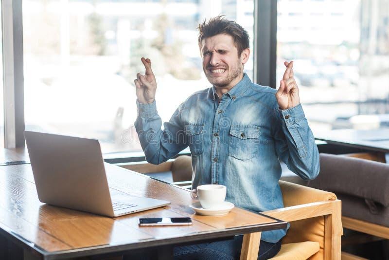 ¡Rogación! El retrato de la vista lateral del freelancer joven barbudo deseoso en camisa de los tejanos se está sentando en café  fotos de archivo libres de regalías