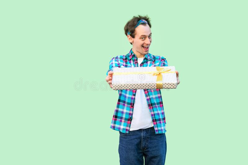 ¡Tómelo! Hombre adulto joven satisfecho del inconformista en la camiseta blanca y la situación a cuadros de la camisa, dándole pr fotografía de archivo libre de regalías