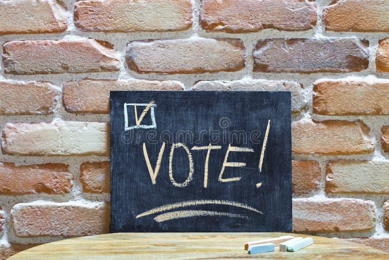 ?Tablero de tiza con la palabra VOTO! ahog?ese a mano y marca con tiza en la tabla de madera en fondo de la pared de ladrillo imagen de archivo