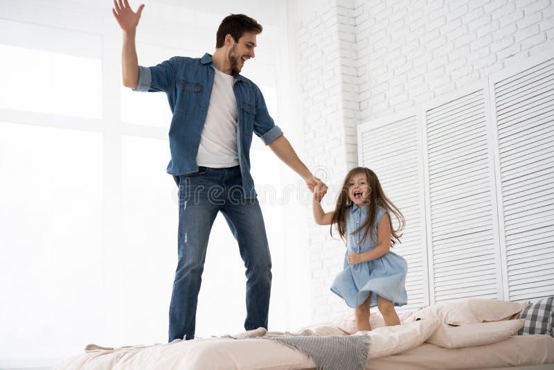 ¡Te amo, papá! El hombre joven hermoso en casa con su niña se está divirtiendo y está saltando en cama ¡Día feliz del ` s del pad imágenes de archivo libres de regalías