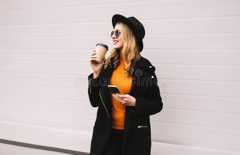 ¡Tiempo de la rotura! La mujer sonriente de la moda que goza del café sostiene smartphone en ciudad en gris fotos de archivo