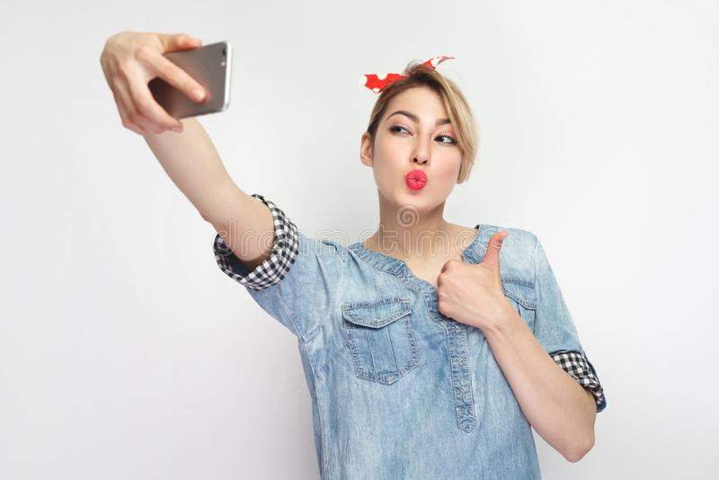 ¡Tiempo de Selfie! Retrato de la mujer atractiva atractiva del blogger en camisa azul casual del dril de algodón con el maquillaj imagen de archivo