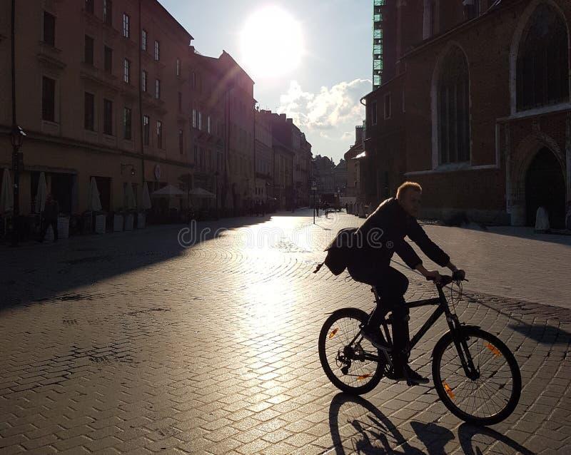 ¡Un ciclista me monta con el siguiente! Un ciclista monta a través de la ciudad en la luz de la mañana ciudad en la luz de la mañ imagenes de archivo
