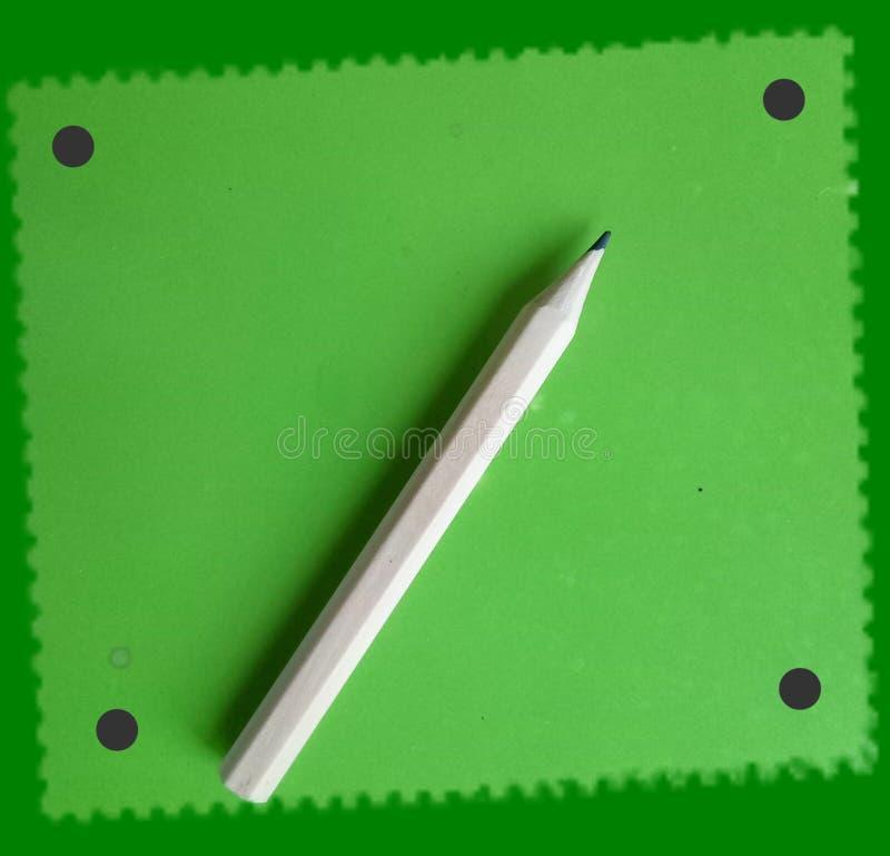 ¡Un pequeño lápiz de madera lindo en notas verdes de un bloque! imágenes de archivo libres de regalías