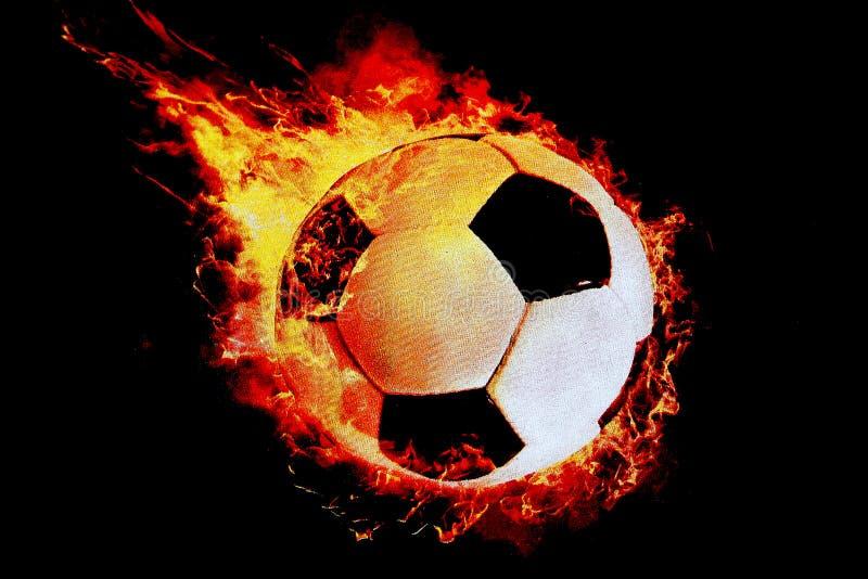 ¡Una bola del fútbol envuelta en fuego vuela en un fondo negro! imagen de archivo libre de regalías