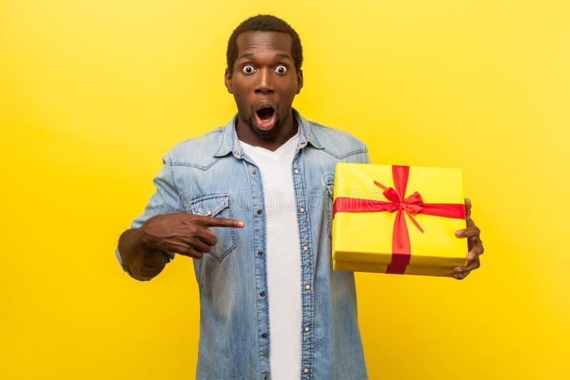 ¡Wow, un regalo increíble! Retrato de un hombre impactado apuntando a una caja de regalo aislado sobre fondo amarillo imagen de archivo libre de regalías