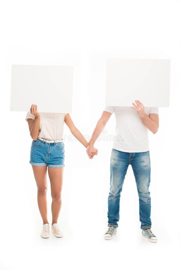 «Ελκυστικά νέα χέρια εκμετάλλευσης ζευγών και κρύβοντας πρόσωπα από τα κενά εμβλήματα, στο λευκό στοκ φωτογραφίες με δικαίωμα ελεύθερης χρήσης