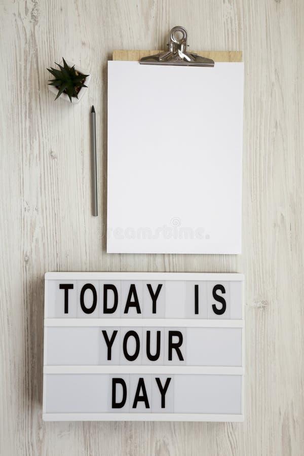 «Dzisiaj jest twój dzień «na lightbox, schowek z pustym prześcieradłem papier na białym drewnianym tle, odgórny widok overhead zdjęcia stock