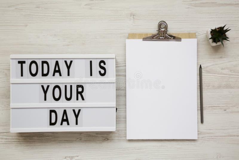 «Dzisiaj jest twój dzień «na nowożytnej desce, schowek z pustym prześcieradłem papier na białym drewnianym tle, odgórny widok ove fotografia stock