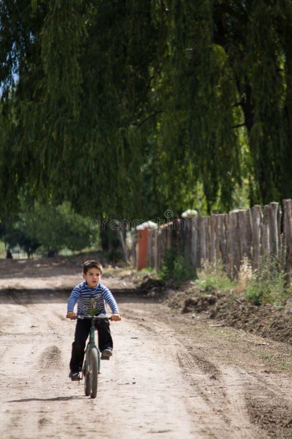 «Mendoza, Argentyna, febrero 17, 2011: chłopiec na bicleta drodze gruntowej ` zdjęcie royalty free