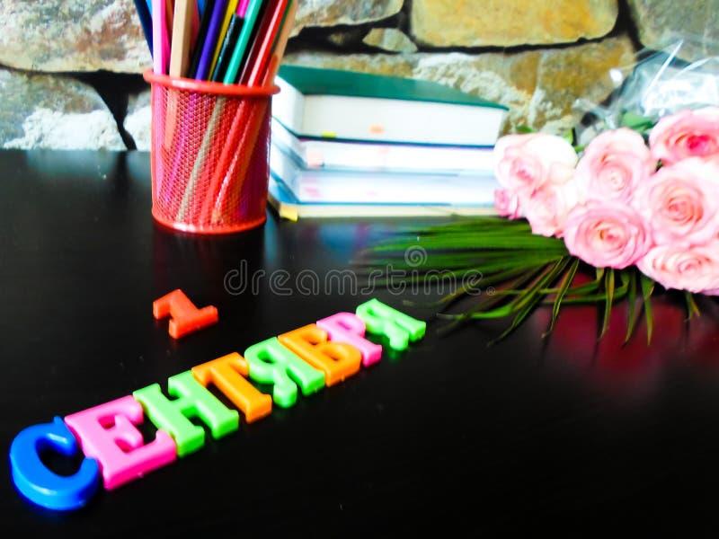 1° settembre concetto Libri, fiori, matite su una tavola nera 1° settembre è la parola nel Russo Di nuovo al banco immagini stock