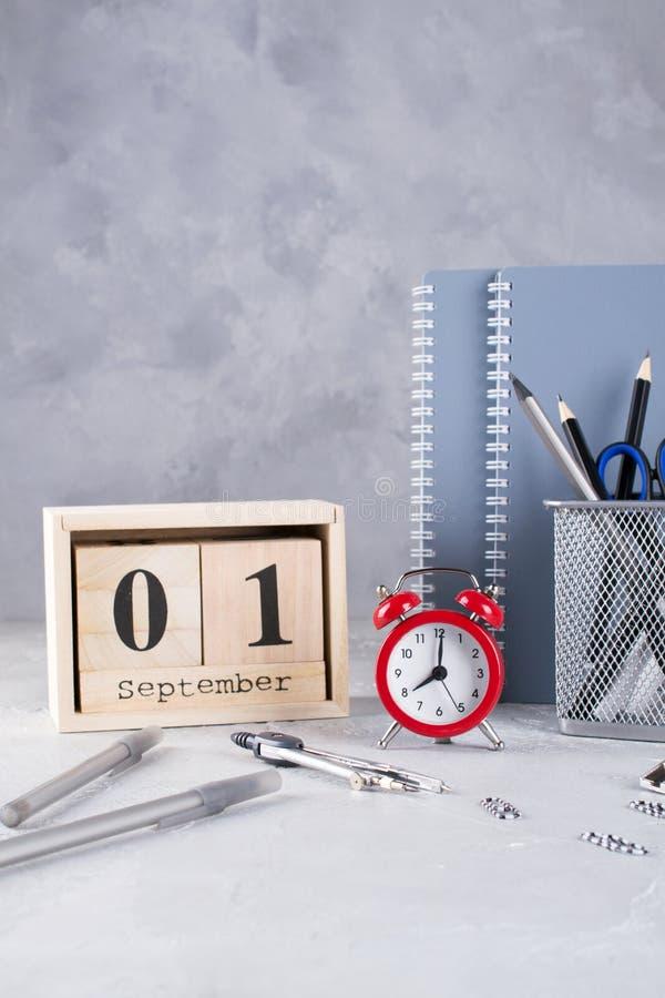 1º de setembro Calendário de madeira, grupo de fontes de escola, despertador vermelho em uma tabela cinzenta imagens de stock royalty free