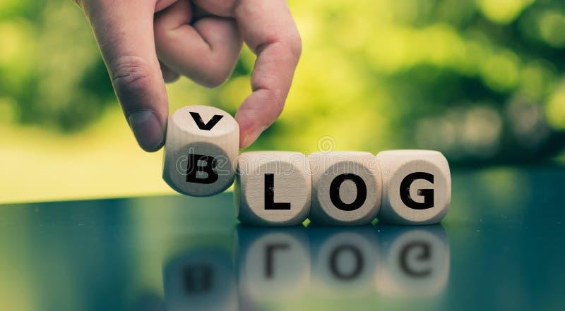 ¿Blog o Vlog? La mano da vuelta a un cubo y cambia la expresión fotografía de archivo libre de regalías