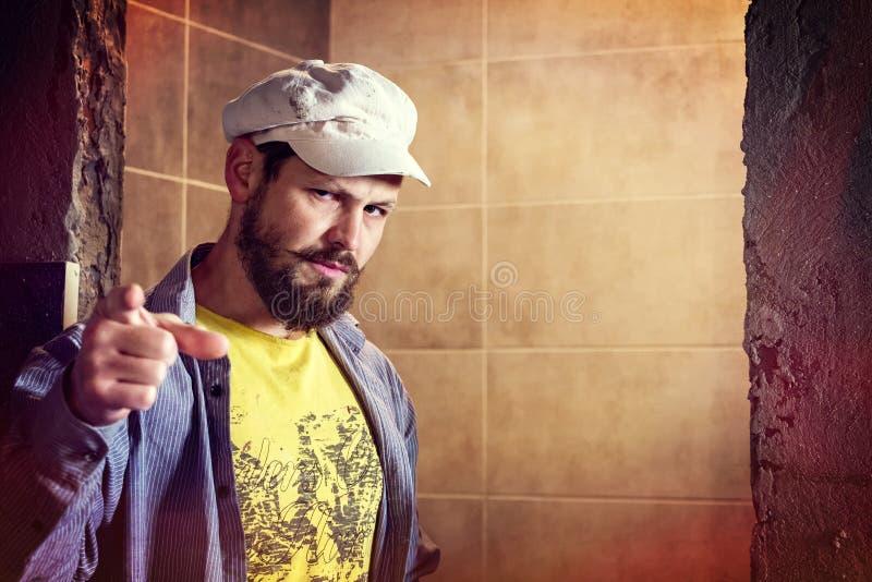 ¿El hombre barbudo brutal en un casquillo de la ocho-cuchilla frunció el ceño indignadamente, señalando su finger a la pregunta ' fotografía de archivo