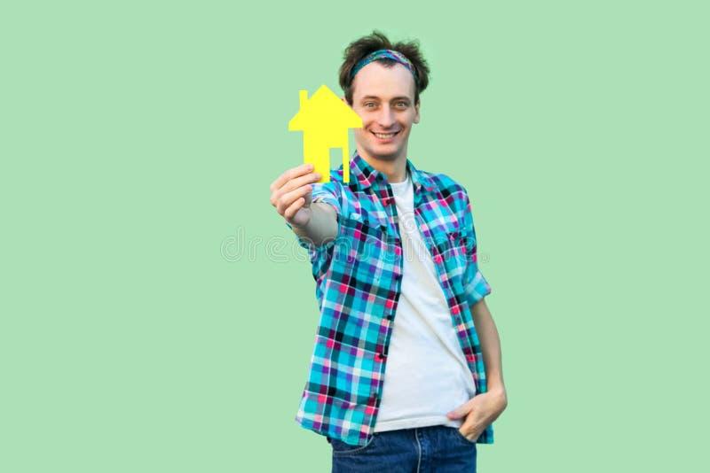 ¿Es usted ideal? Hombre joven satisfecho feliz del agente inmobiliario en la camisa a cuadros que sostiene la pequeña casa de pap imagenes de archivo