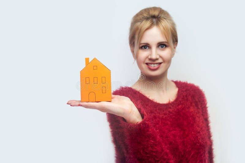 ¿Es usted ideal? Mujer joven satisfecha feliz del agente inmobiliario en la situación roja de la blusa, sosteniendo la pequeña ca foto de archivo
