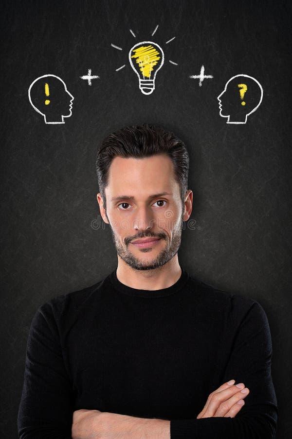 ¿Hombre joven con los brazos cruzados, cabezas con? ¡! símbolos y bulbo-idea ligera en un fondo de la pizarra foto de archivo libre de regalías