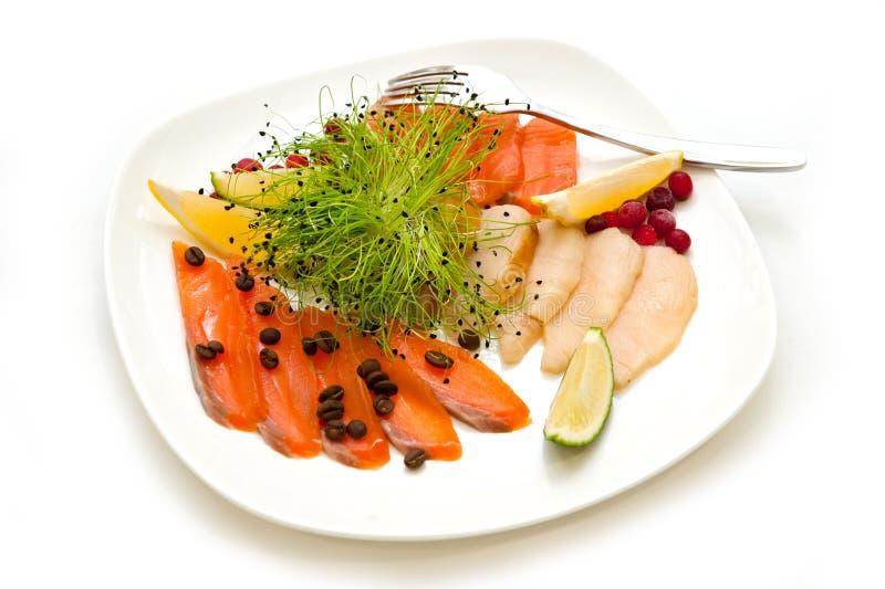 ¿Plato con cortado?? pescados rojos con los granos y las bayas de café de la fruta cítrica foto de archivo